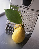 A lemon with a leaf in front of a grater