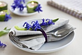 A place setting with a napkin, cutlery and hyacinths
