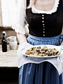 Woman serving buckwheat pockets with cabbage