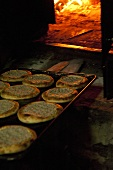 A tray of unleavened bread in front of a woodfired oven