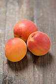 Three apricots on a wooden surface