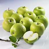 Wet Granny Smith apples, whole and halved