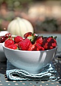 A bowl of fresh strawberries, cherries and melon
