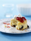 A raisin scone with strawberry jam