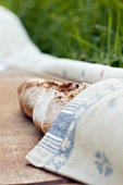 A baguette wrapped in a napkin for a picnic
