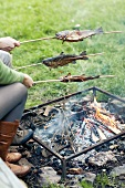 Fish being grilled over a fire