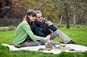 Pärchen macht Picknick auf Wiese im Herbst