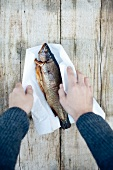 Hands holding grilled fish wrapped in paper