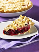 A slice of blackberry and raspberry crumble pie with slivered almonds