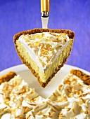 A piece of coconut cream pie on a cake slice
