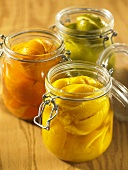 Three open jars of preserved lemons, oranges and limes