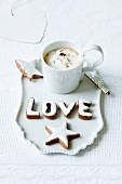 A cinnamon star and letters with a cup of cappuccino