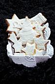 Mürbteigplätzchen mit weißem Zuckerguss auf Tortenpapier