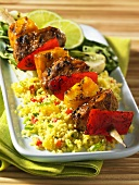 A grilled pork and mango kebab on a bed of couscous