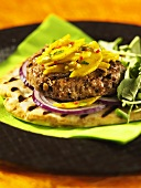 A lamb burger on flat bread with red onions and mango