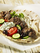 A pitta bread filled with a lamb kebab, cucumber, olives and tzatziki (Greece)