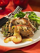 A pork chop with maple syrup and apples on wild rice