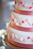A three tier wedding cake in pink and white