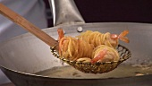 Taking deep-fried noodle-wrapped prawns out of wok