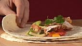Tortilla mit Hähnchenbrust und Salsa aufrollen