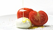 Preparing tomatoes with mozzarella and basil