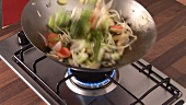 Tossing vegetables and sprouts in a wok
