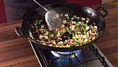 Cooking vegetable rice in a wok