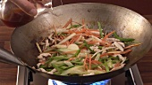 Sautéing chicken and vegetables in a wok, adding soy sauce