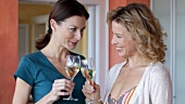 Two women clinking glasses of white wine