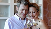 Man and woman clinking glasses of white wine