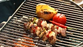 Meat kebabs, potato and tomato on a barbecue