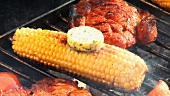Corn on the cob with herb butter & pork neck steaks on barbecue