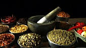 Assorted spices in small containers and a mortar and pestle
