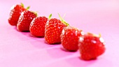 Fresh strawberries on pink background