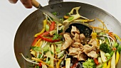 Cooking vegetables in wok and adding chicken fillet