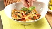 Making ravioli with spinach filling and tomato sauce