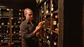 Young man taking a bottle of wine from a wine rack