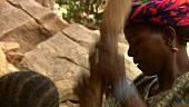 African women crushing cereal grains with wooden sticks