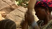 Afrikanerinnen zerkleinern Getreidekörner mit Holzstöcken