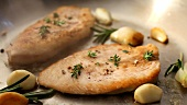 Turkey breast with garlic and herbs in a frying pan
