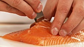 A salmon fillet being deboned (German Voice Over)