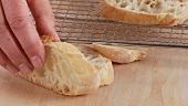 Ciabatta slices being placed on an oven rack