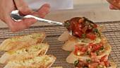 Bruschetta zubereiten: angemachte Tomaten auf den Brotscheiben verteilen