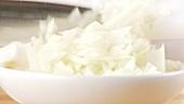 Klein geschnittene Zwiebeln in ein Schälchen geben
