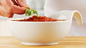 Garnishing tomato sauce with basil