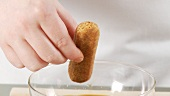 Preparing tiramisu: dunking a sponge finger into espresso and placing in a dish