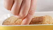 Preparing tiramisu: adding another layer of sponge fingers