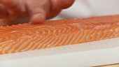 Removing the bones from a salmon: exposing the bones by running a finger down the length of the fillet