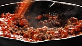 Bolognese sauce being stirred in a pan
