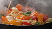 Peppers and onions being fried and stirred in a pan